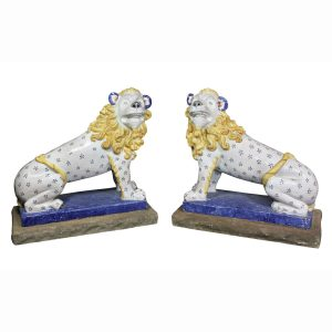 A true pair of large French glazed pottery lions each seated and attached to a stone base